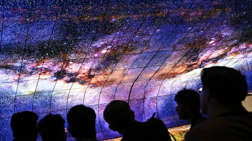 People watch a television installation at the booth of LG during a press preview at the IFA in Berlin