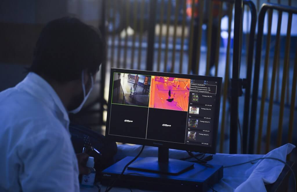 A railway employee monitors thermal images on a screen as passengers arrive to board a train to Rawalpindi at a station after the government eased a lockdown imposed to prevent the spread of the COVID-19 coronavirus in Lahore