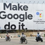 Indian commuters ride past an advertisement poster of Google in Bangalore