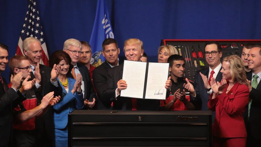 President Donald Trump signs an executive order to try to bring jobs back to American workers and revamp the H-1B visa guest worker program during a visit to the headquarters of tool manufacturer Snap-On in Wisconsin.