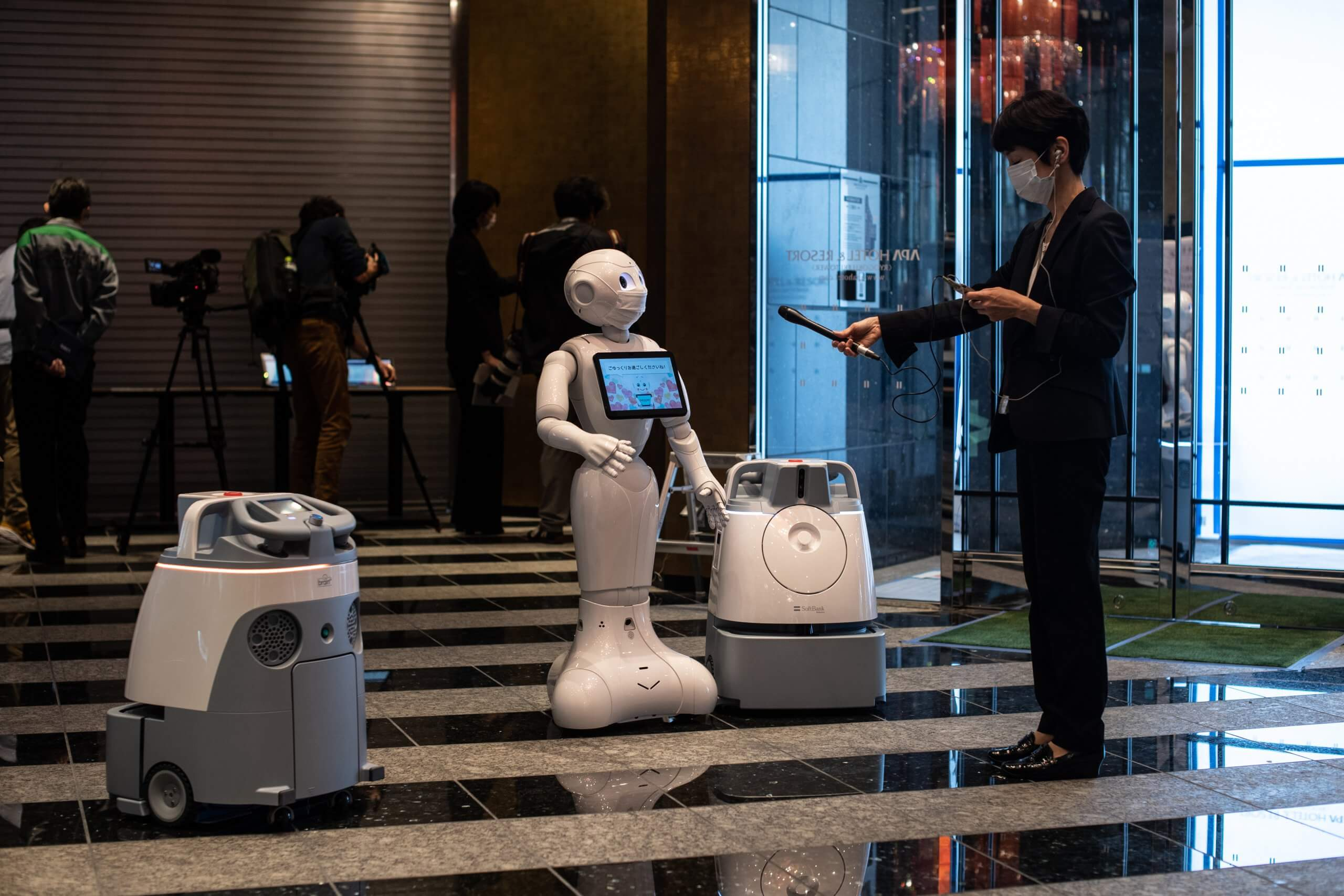 Pepper with two other cleaning robots in the lobby of a hotel