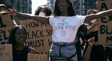 Black Lives Matters protesters in London holding signs and marching outside American Embassy
