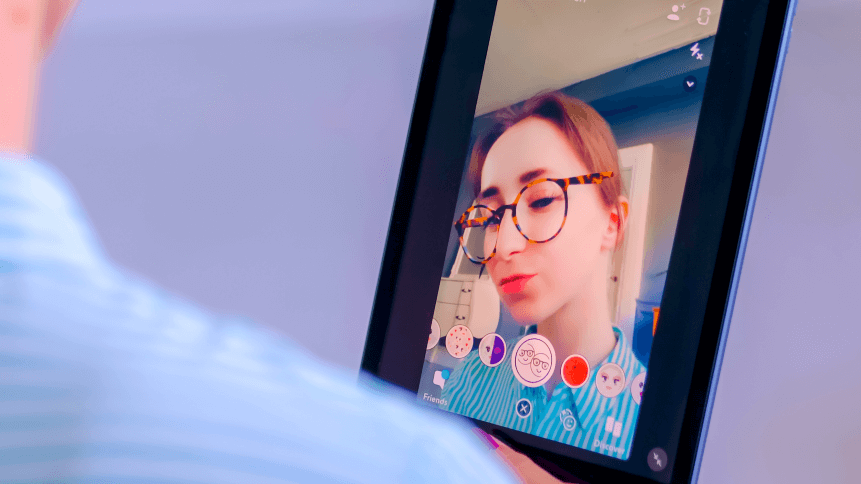 Snapchat multimedia messager with 3d face mask filter on tablet in woman hands at home. Face detection technology, AR, social media, selfie, entertainment concept